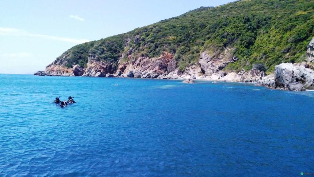 Дайверы в ярко синей воде океана возле Нячанга